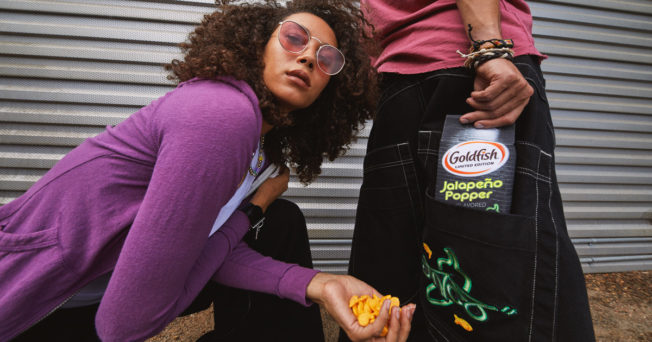 A woman posing next to a person holding Goldfish Crackers in JNCO jeans