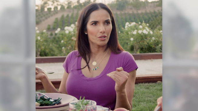 Padma Lakshmi sits at an outdoor table while eating and talking to someone off camera