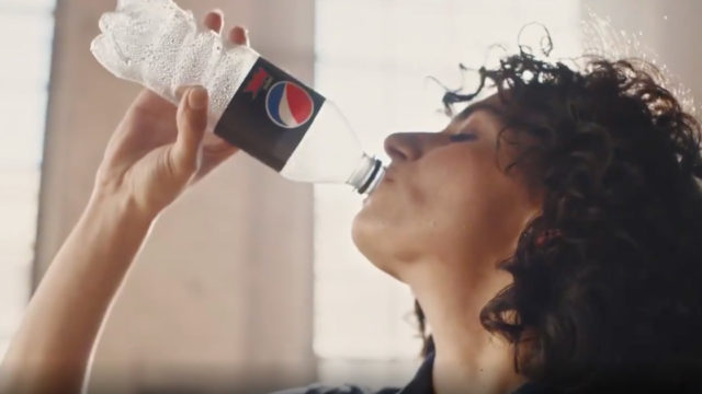 A woman drinks from a recycled Pepsi Max bottle