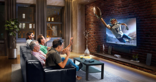 Photo of a family watching tv and reacting to a football player emerging from the screen to catch a football.