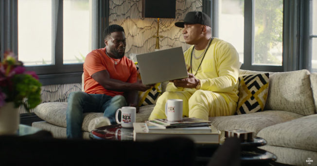Kevin Hart and LL Cool Ja on a couch looking at a laptop