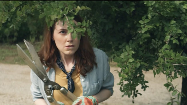 A woman looks suspiciously through bushes while holding garden shears