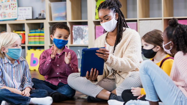 a teacher and student wearing masks in the classroom