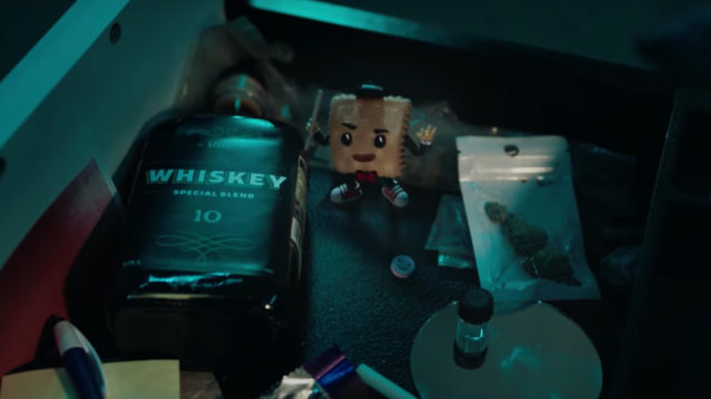 A cartoon cracker standing between whisky and drugs