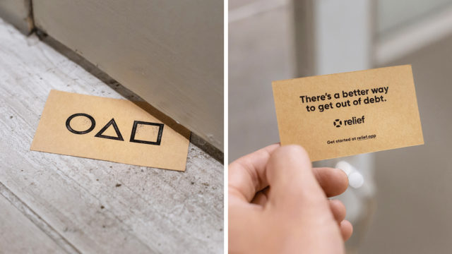 A small card on the ground has a circle, triangle and square on one side, with a message about getting out of debt on the reverse