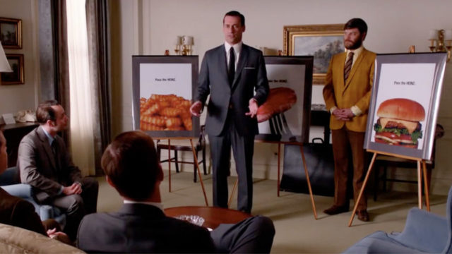 Still from Mad Men-men in suits going over storyboards.