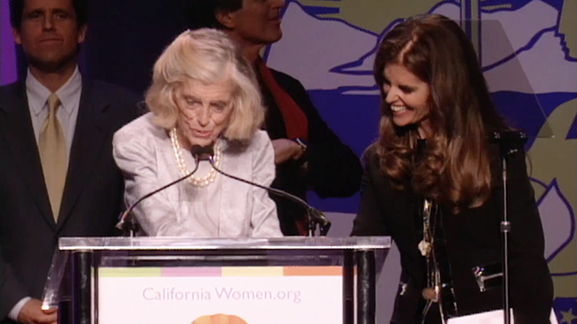 Eunice Kennedy Shriver and Maria Shriver stand at a podium.
